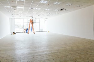 Electricians with stepladders are working on ceiling of a large white and empty showroom