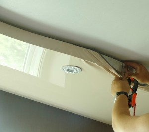 Master repairs stretch ceiling with installed luminaire